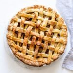 a classic lattice apple pie on a white background with a grey linen