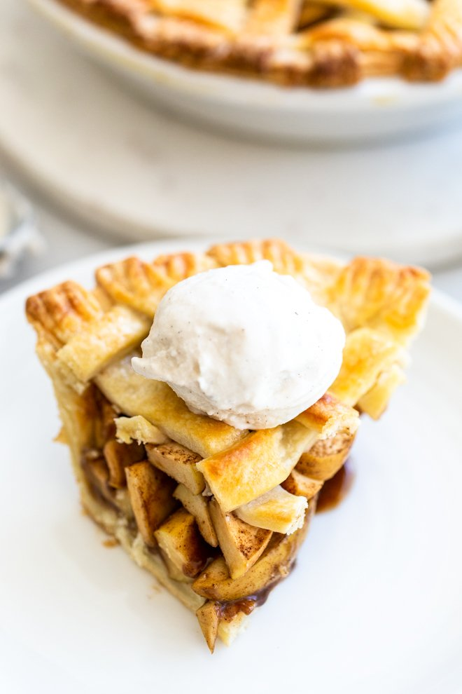 a slice of apple pie with ice cream on a white plate