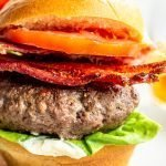 burgers with bacon, lettuce and tomato on a white background