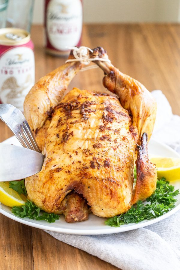 roasted chicken on a platter on a wood table