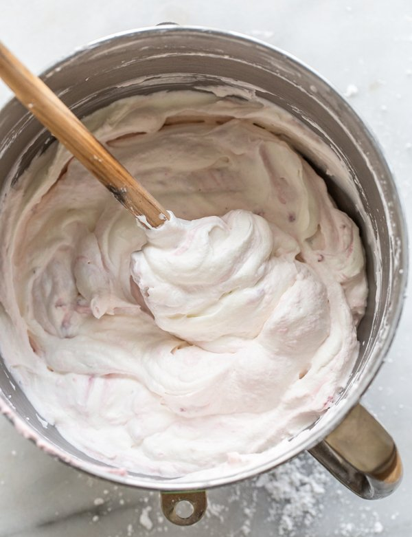 whipped cream in a metal bowl with a spatula folding in