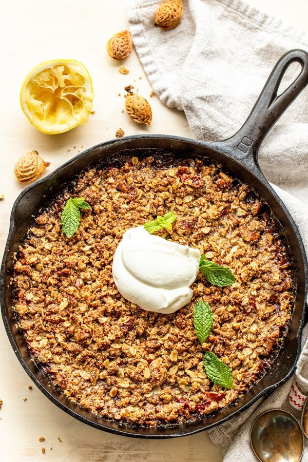 Gluten free peach crisp in a skillet with a dollop of greek yogurt and mint