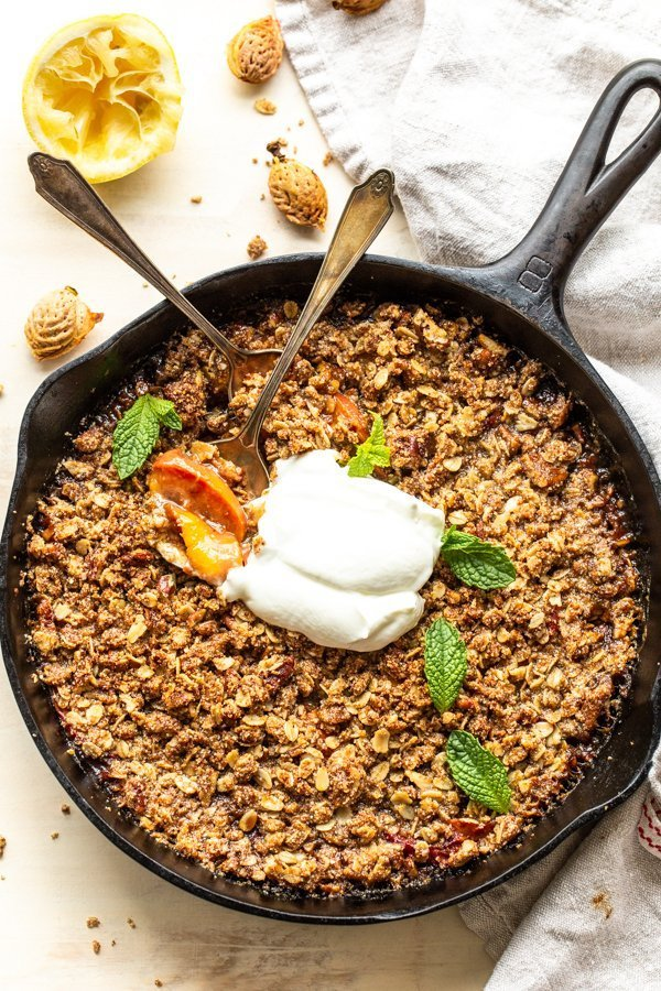 peach crisp with spoons eating the crisp on a white background