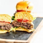 juicy elk burgers with lettuce, tomato and cheese cut in half on a wood and slate board with a white background