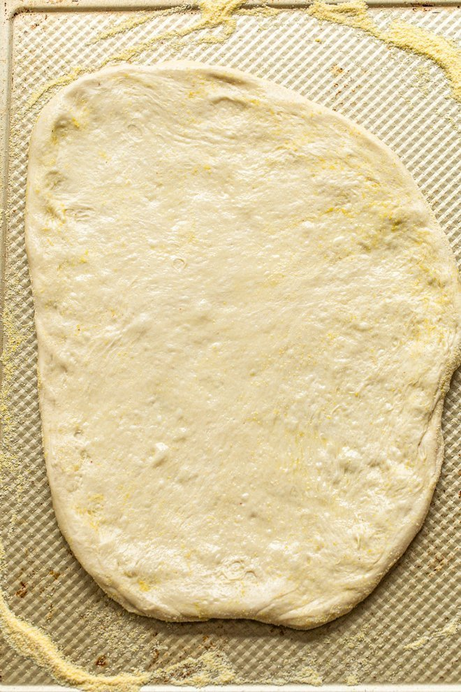 pizza dough stretched on a baking sheet