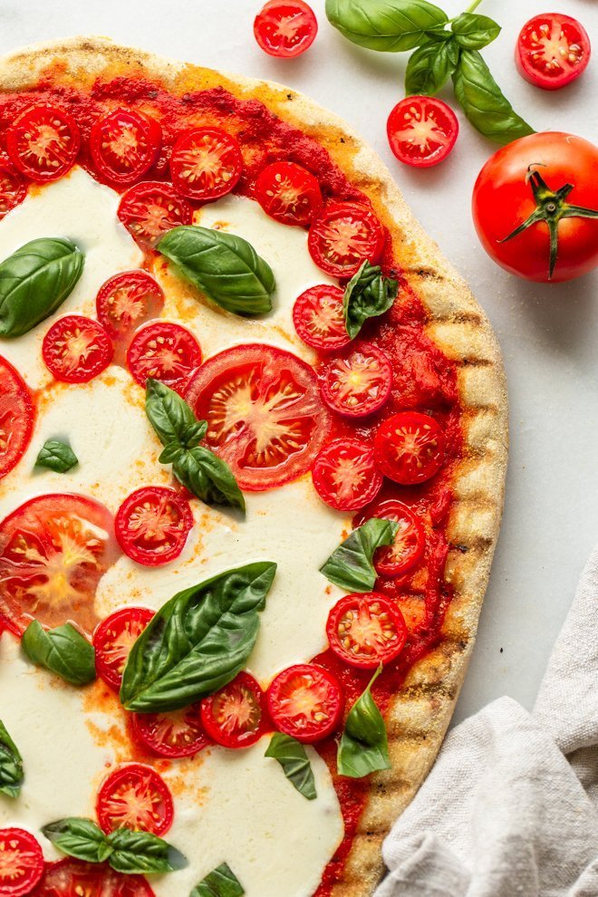 Traeger grilled pizza recipe cut on a marble slab with fresh basil, roma and cherry tomatoes