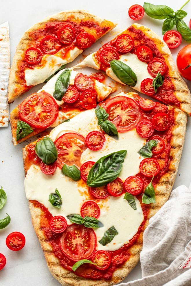 Traeger grilled pizza recipe cut on a marble slab with fresh basil