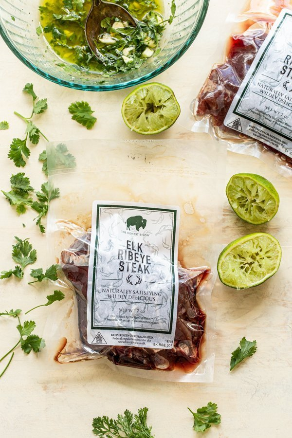 elk steaks on a cream board with cilantro and lime halves