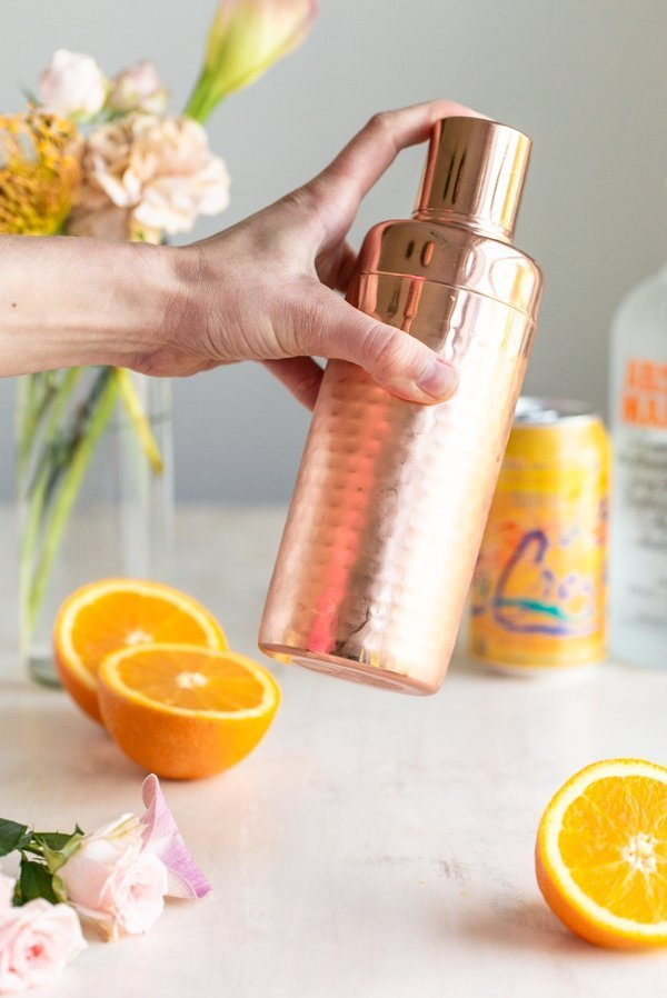 shaking a copper cocktail shaker with oranges and flowers in the background