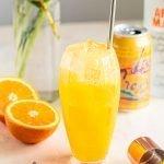 an orange crush in a clear tall glass