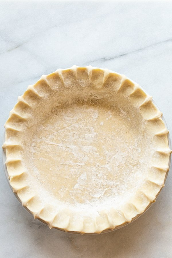 unbaked pie crust on a marble slab