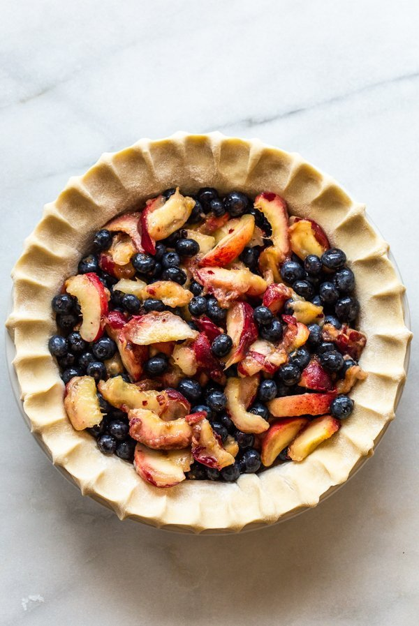 blueberries and peaches in unbaked pie crust