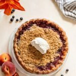 peach blueberry pie with a crumble topping on a cream board with a striped linen napkin