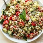 quinoa tabbouleh salad with a mint leaf in a white bowl on a tan background