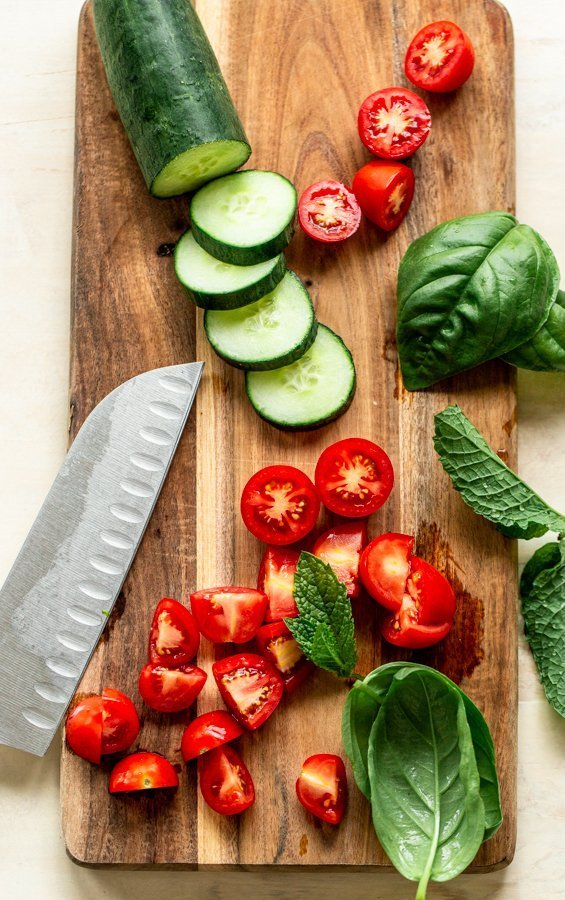 sliced cucumbers and tomato on a wood board with a knife