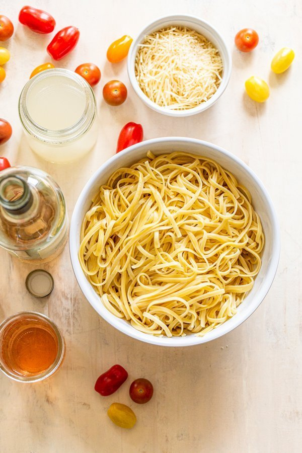 pasta in a bowl and all of the ingredients for a fresh tomato pasta dish