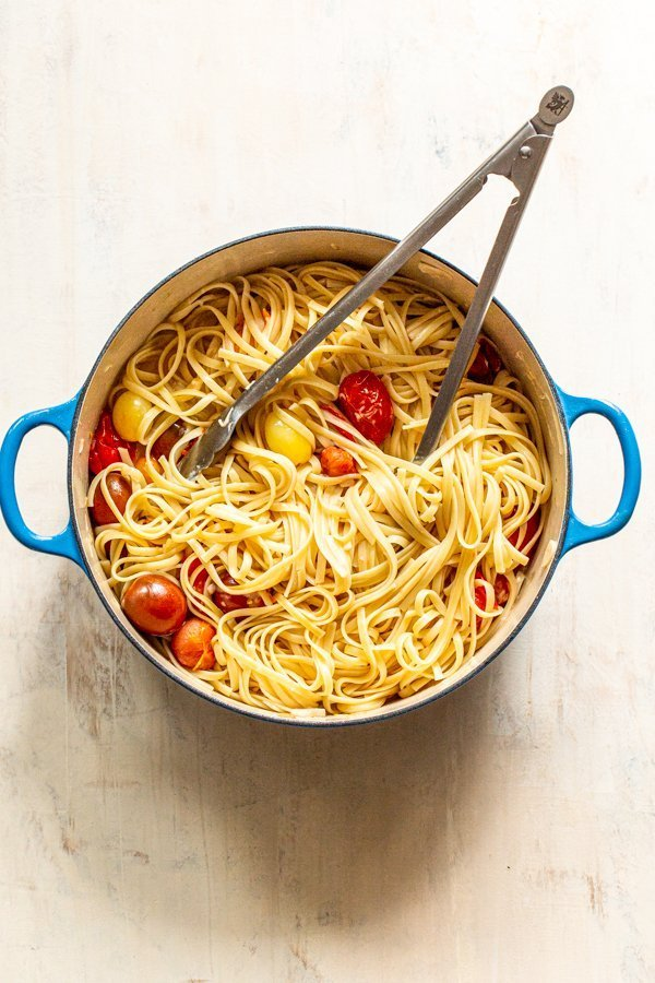 pasta in a pot being tossed with tongs