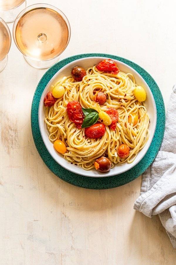 summer pasta with tomatoes and cheese in a white bowl on a blue charger with rosé wine