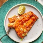 traeger smoked salmon with a sweet and spicy glaze on a blue plate and a lime