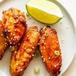 air fryer chicken wings on a cream plate with a lime