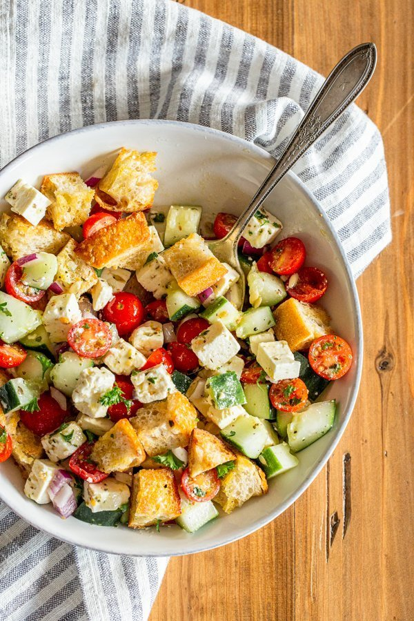 Green Panzanella salad in a white dish with a striped napkin on a wood table