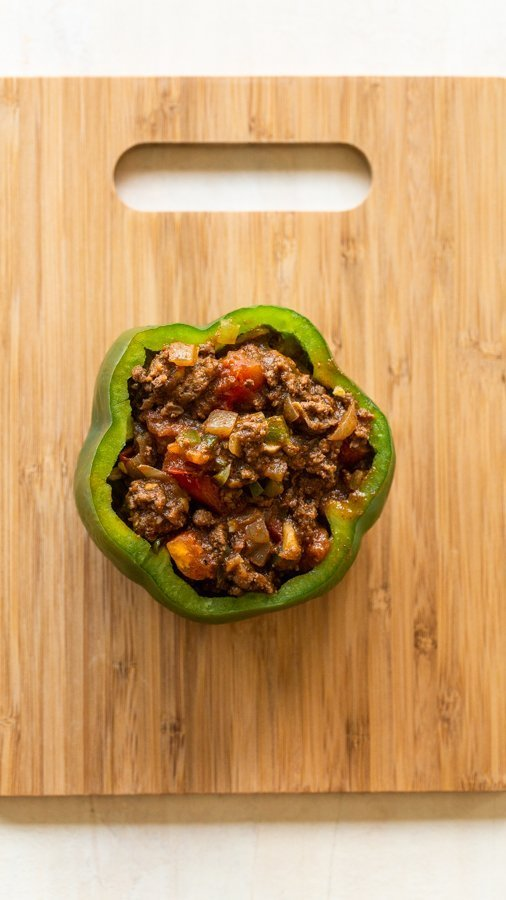 a stuffed pepper, pre cooked on a wood cutting board