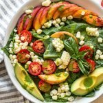 a late summer salad with corn, tomatoes and peaches in a white bowl with avocado slices and green dressing