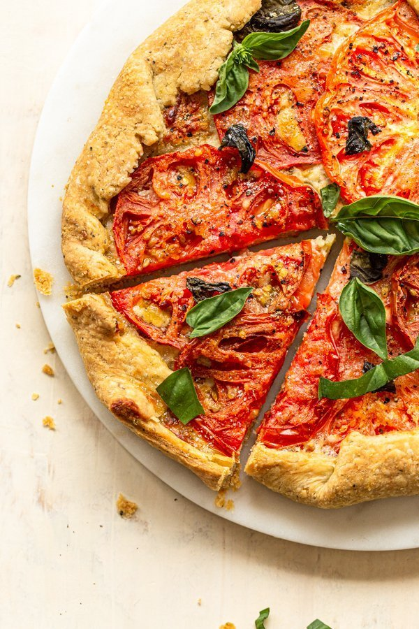 flakey pie crust in a tomato galette with basil and a slice cut out