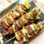 Chipotle steak kabobs with peppers and onions on a cutting board with black slate