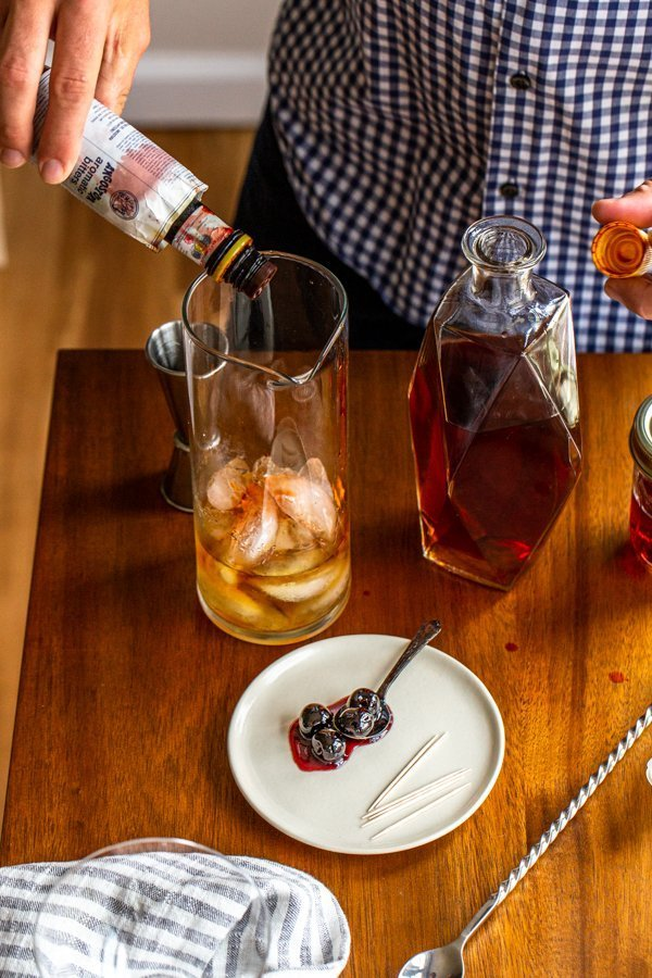 dropping aromatic bitters into a cocktail pitcher