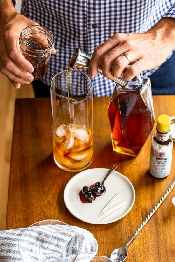 pouring vermouth into a cocktail pitcher