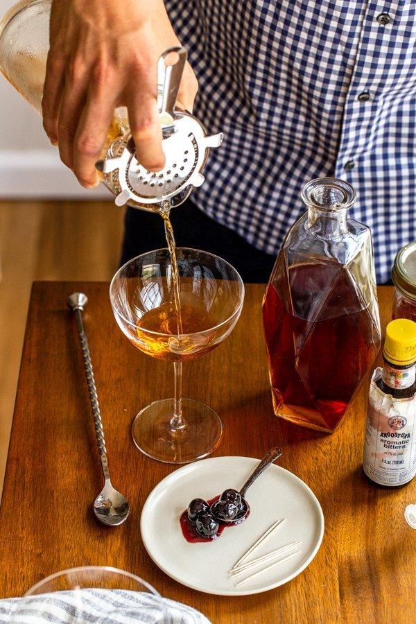 pouring a manhattan cocktail from a cocktail pitcher