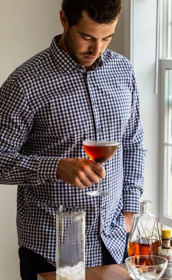 man holding a drink by a window in a blue check shirt