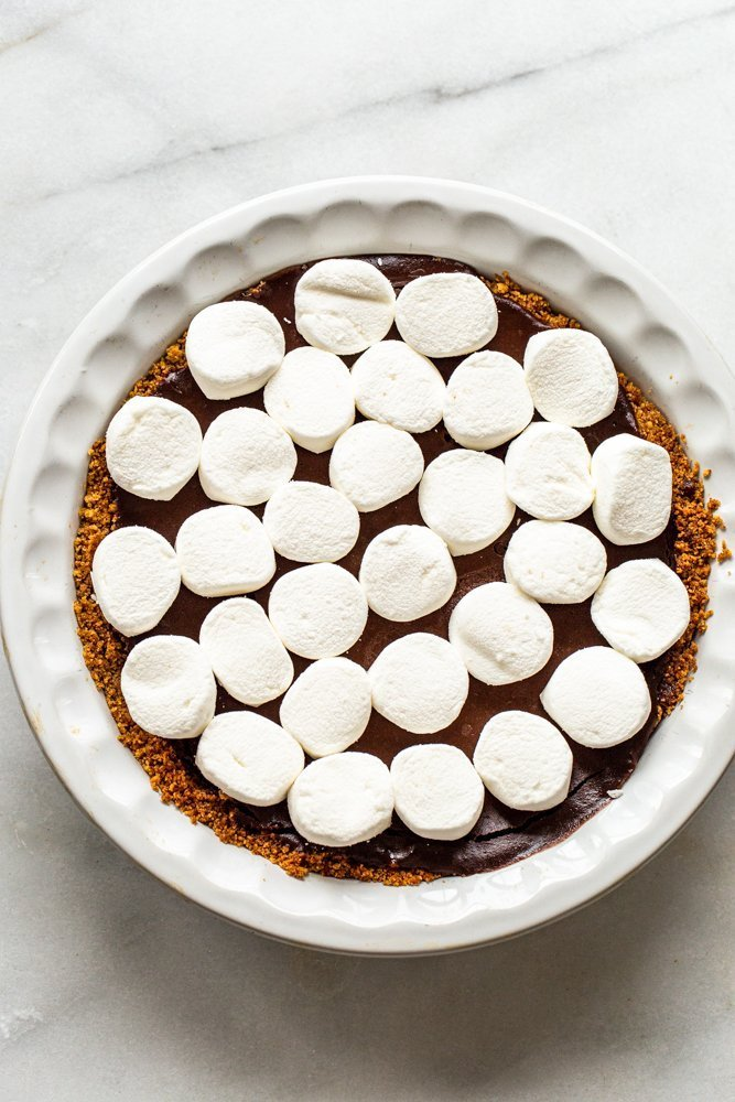 marshmallows on a chocolate pie with a graham cracker crust