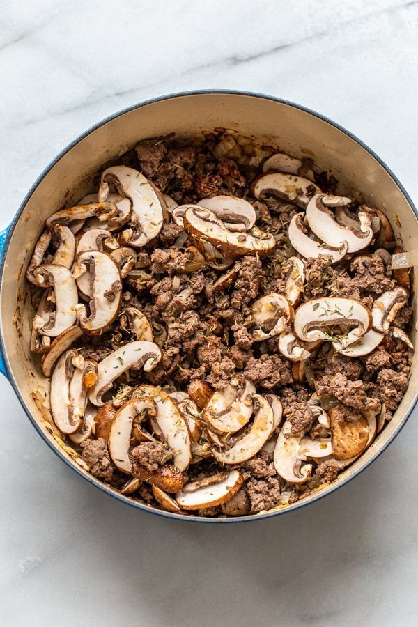 mushroom and ground venison cooking in a dutch oven
