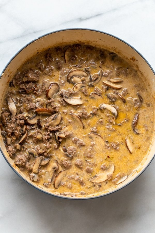 mushrooms and ground venison in sauce in a dutch oven