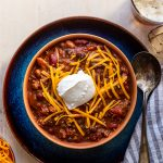 beer chili with cheese and sour cream in an orange bowl in a blue plate