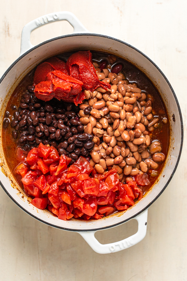 beans and tomatoes in a white pot