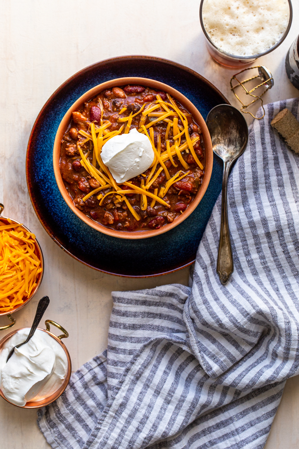 chili with cheese and sour cream in an orange bowl in a blue plate