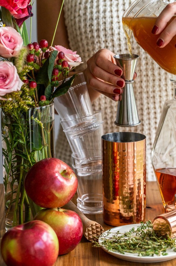 pouring cider syrup into a copper cocktail shaker with stacked glasses, flowers and apples