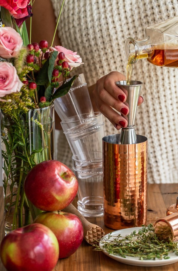 pouring bourbon into a copper cocktail shaker with stacked glasses, flowers and apples