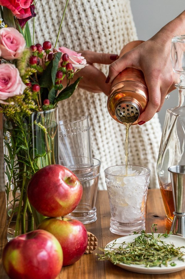 pouring cider bourbon smash from a copper cocktail shaker into a glass with stacked glasses, flowers and apples