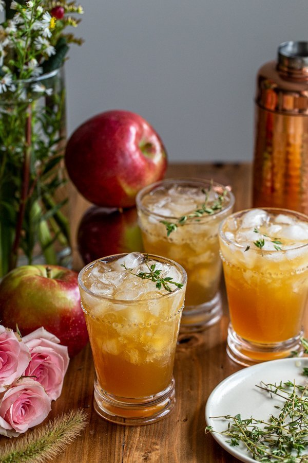 apple cider bourbon smash on a wood board with roses and apples and thyme