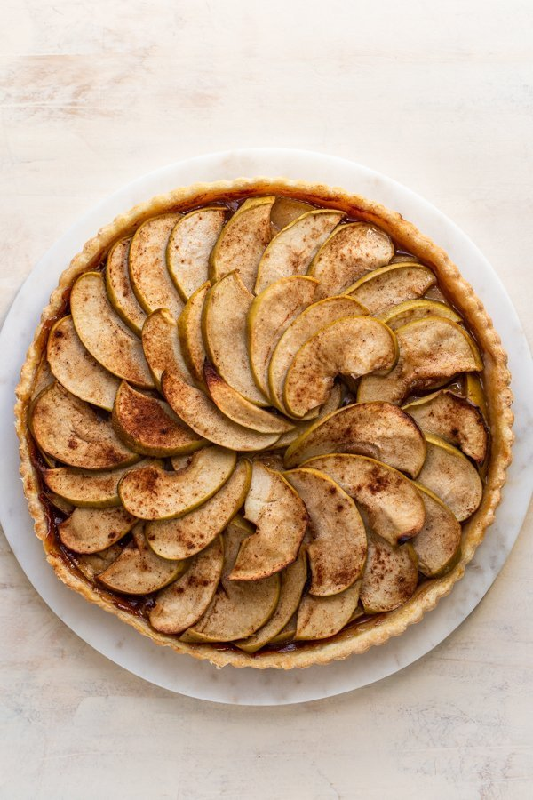 a baked apple tart on a cream background