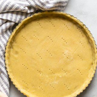 gluten free pie crust in a tart shell with a striped linen