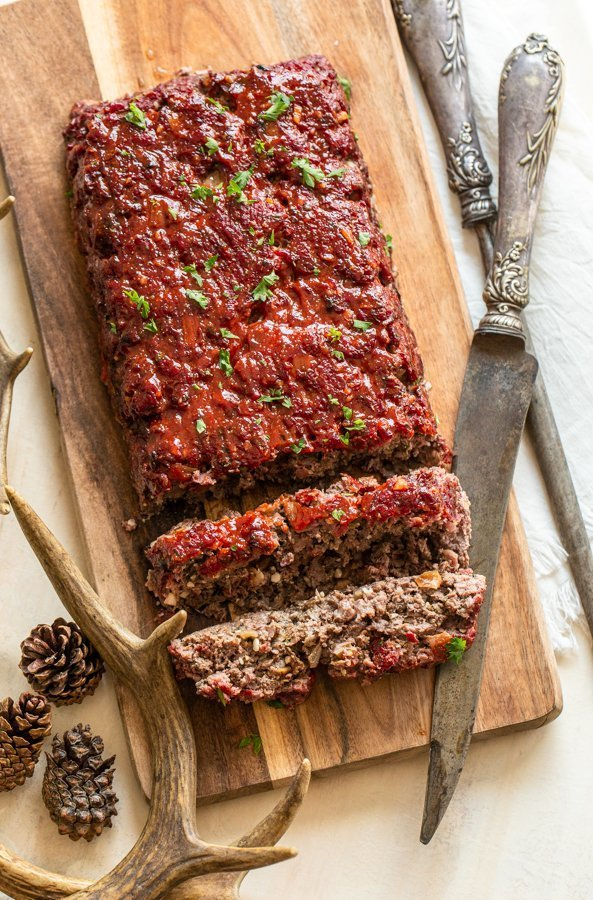 sliced smokey venison meatloaf on a wood platter with a knife