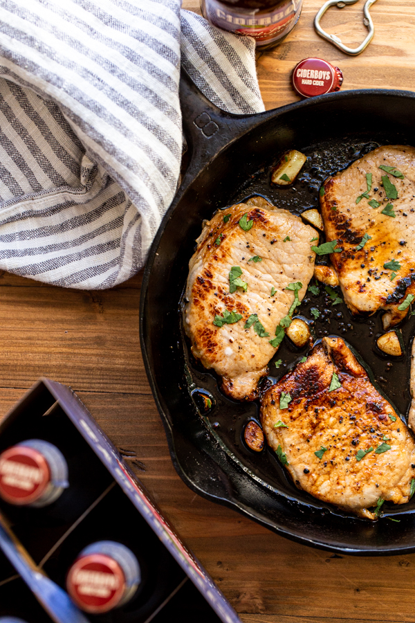pork chops in a skillet with garlic and hard apple cider
