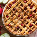 cranberry apple pie on a wood board with a pink napkin, apples and cranberries