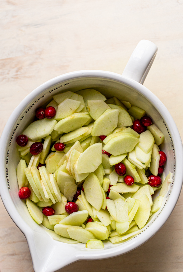 apples and cranberries in a white bowl