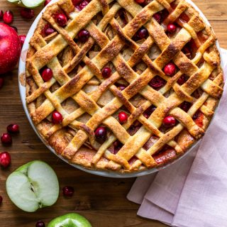 apple cranberry pie on a wood board with a pink napkin, apples and cranberries